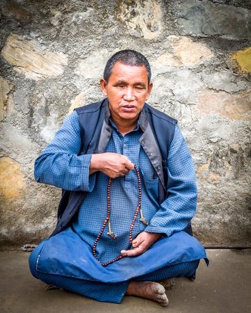 blind man: Kathmandu,Nepal - May 21,2016 : A blind man praying with prayer beeds in swayambhunath stupa on Buddha Jayanti or 2560th Buddhas Birthday. Editorial