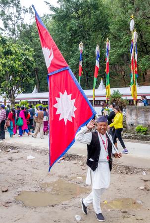 nepali: Kathmandu,Nepal - May 21,2016 : An old man with the flag of Nepal in Nepali national dress in swayambhunath on Buddhas Birthday.Prayers are walking to round the Swayambhunath Stupa at the back.