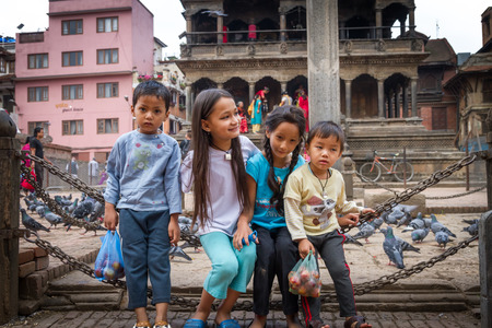 nepali: Kathmandu,Nepal - March 26,2016: Smiling cute Nepali childs playing on the Iron chains are feeling shy to pose for photographs.