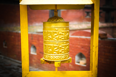 tibetian: Yellow coloured Prayer Wheel in a blurry background photographed in Kathmandu,Nepal. Stock Photo