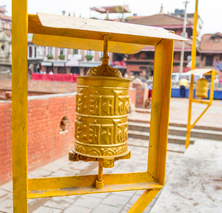 ohm: Yellow coloured Prayer Wheels placed at the Patan Durbar Square in Kathmandu,Nepal.