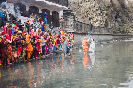 Kathmandu,Nepal - Feb 12,2018: Hindu devotees with bare foot and holy water pots offering Holy Water to Lord Shiva. This is on the occasion of Bol Bom and Mahashivaratri Festival at Pashupatinath Temple,Aryaghat. Editorial