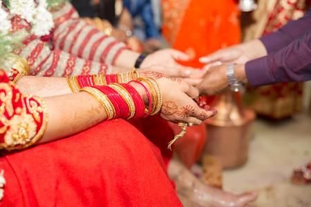 Manos de la novia y el novio hindú nepalí en el día de la boda.