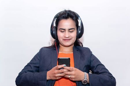 Pretty Asian girl listening music with her headphones in Smart Phone in office.Mobile
