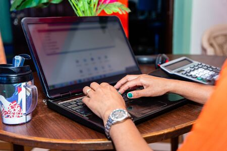 Asian Freelance woman working from home in lockdown time of Covid19. Close up hand with laptop.