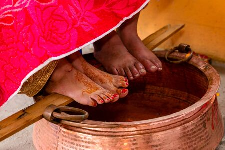 Close up Shot of Feet of bride and groom during Traditional Hindu Wedding ceremony. Bride relatives wash feet and drink holy water according to the culture.