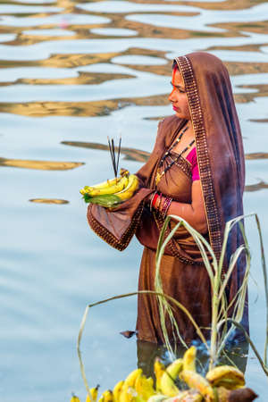 Kathmandu,Nepal - November 1,2019: Hindu devotee offering prayers to sun god standing in water according to hindu rituals during Chhath Puja Festival in Kathmandu. Chath Puja rituals