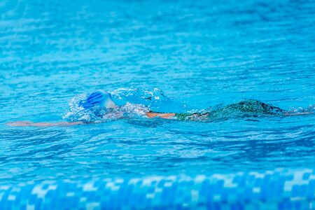 Unknown person swimming in a sparkling blue pool Standard-Bild - 148388783