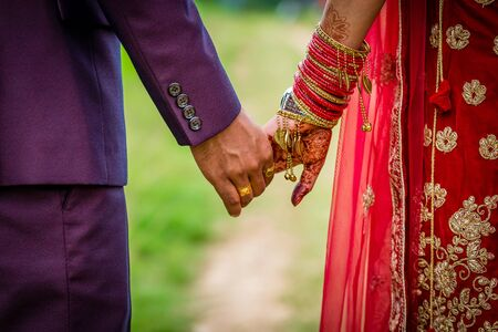 Young adult male groom and female bride holding hands together,Hands of newlywed couple.