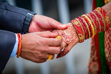 Young adult male groom and female bride holding hands together,Hands of newlywed couple. Standard-Bild - 148388829
