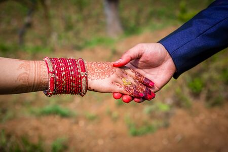 Young adult male groom and female bride holding hands together,Hands of newlywed couple. Standard-Bild