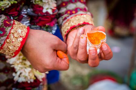 The Groom's hand holding sindur or Vermilion before applying on the bride`s hair-parting.Selective Focus