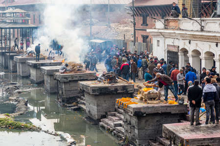 Kathmandu,Nepal - February 12,2018: Hindu People Cremating dead bodies according to hindu rituals at Bagmati River Pashupatinath Temple premises in Kathmandu. This is the most sacred place for Hindus all over the world. Hindu Cremation Ghats