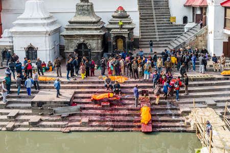 Kathmandu,Nepal - February 12,2018: Hindu People offering religious prayers to the dead bodies before cremating at Bagmati River Pashupatinath Temple premises in Kathmandu. This is the most sacred place for Hindus all over the world. Hindu Cremation Ghats