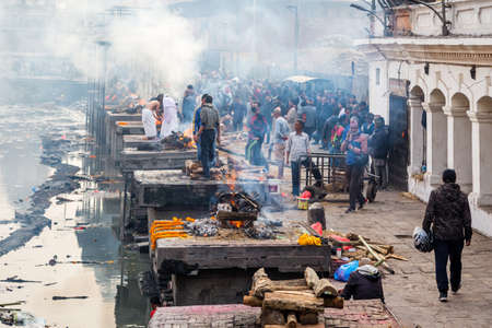Kathmandu,Nepal - February 12,2018: Hindu People Cremating dead bodies according to hindu rituals at Bagmati River Pashupatinath Temple premises in Kathmandu. This is the most sacred place for Hindus all over the world. Hindu Cremation Ghats Standard-Bild - 148375159