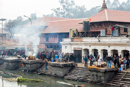 Kathmandu,Nepal - February 12,2018: Hindu People Cremating dead bodies according to hindu rituals at Bagmati River Pashupatinath Temple premises in Kathmandu. This is the most sacred place for Hindus all over the world. Hindu Cremation Ghats Standard-Bild - 148375161