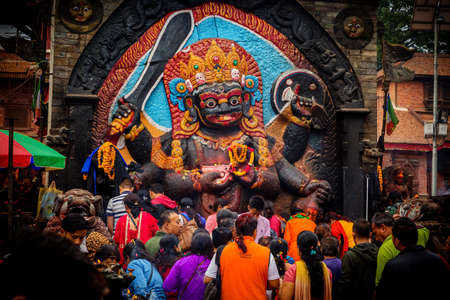Kathmandu,Nepal - June 28,2019: Devotees worship Kal Bhairav which represents deity Shiva in his destructive manifestation. Hindu God Kal Bhairav Standard-Bild - 148475697