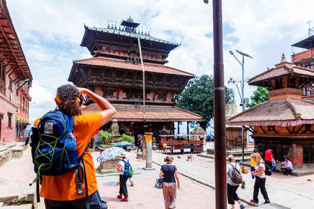Kathmandu,Nepal - August 15,2019: Tourist Taking a photo at Bagh Bhairav Temple Kathmandu Nepal.Tourist Travel Destination in Kathmandu.Places to visit in Kathmandu. Selwctive Focus on Man