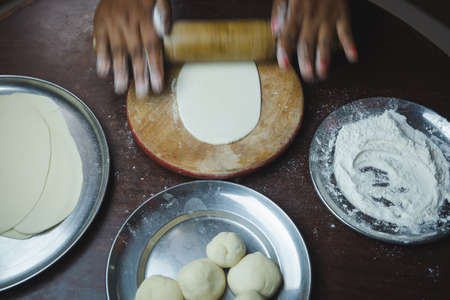 Close up of woman hand rolling dough with rolling pin on kitchen counter table