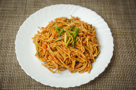 Veg Hakka Schezwan noodles served on a white plate with green onions. selective focus