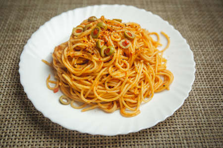 Tasty appetizing classic italian spaghetti pasta with tomato sauce, Olive and basil on plate. View from above, horizontal Standard-Bild