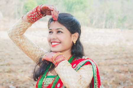 Beautiful Asian Indian Nepali Bride Wearing Ethnic Traditional Outfit with Gold Jewellery and Henna Design in Hand Posing for wedding photoshoots. Smiling Nepalese Bride