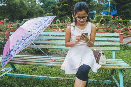 Young asian girl with umbrella. Pretty young girl posing for photograph outdoor.