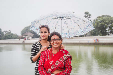 Asian happy mother and daughter traveling outdoors in summer. Family tourism. Asian Nepali women. women posing for photograph