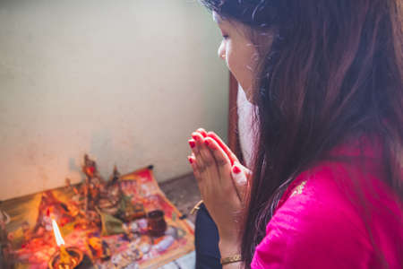 Hindu woman offering paryers to god at home. Hindu devotee praying with god by doing Namaste. Nepali girl worshiping god during depawali festival. Selective focus Standard-Bild