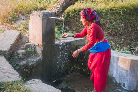 Nepali village woman washing face with water at the local tap placed in the rural village of Nepal. Nepali rural village woman Standard-Bild