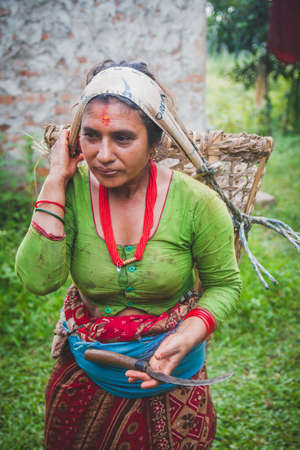 Nepali village woman carrying basket in traditional style in the rural village of Nepal. Nepalese woman Standard-Bild