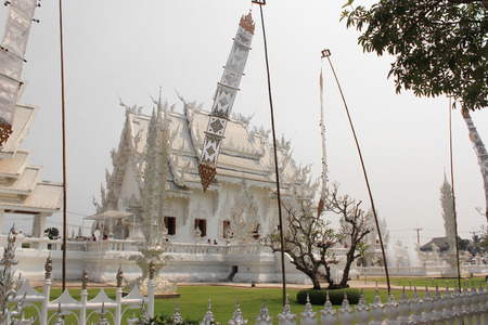 Wat Rong Khun or White Temple, a contemporary unconventional Buddhist temple in Chiangrai, Thailand, with white Lanna style flags photo