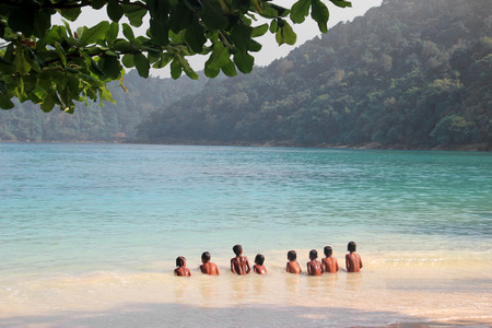 Children swim happily together in the sea of Surin Island in the south of Thailand photo