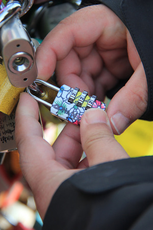 A man is locking a key on the fence on N Seoul Tower as a symbol of promise for their forever loves   photo