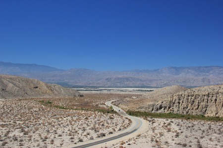 a mirage: Road going through Desert Area near Thousand Palms Oasis Preserve in the Coachella Valley Preserve System, Southern California, United States of America Stock Photo