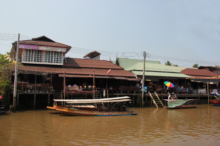 Samutsongkram, Thailand - March 16, 2013: Amphawa, home to the second most popular floating market, is full of Thai canal side way lifestyle and the old traditional way of selling vegetables, fruits and many more from small boats. Editorial