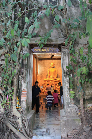 Samutsongkram, Thailand - March 16, 2013: Ancient Buddha called Nin Mani Buddha or Luang Phor Dum is inside the small chapel that is almost completely covered by the roots of a banyan tree at Bangkung Temple in Samutsongkram, Thailand. As one of offical U