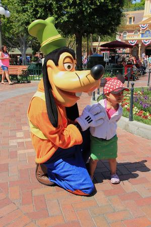main street: Anaheim, California, USA - May 30, 2014: Goofy, a Disney cartoon character, is greeting tourists at Main Street, U.S.A. in Disneyland Park, California. Editorial