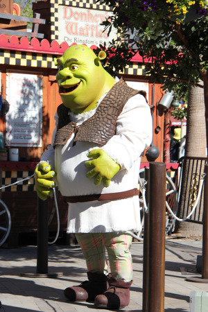 theme parks: Los Angeles, California, USA - March 12, 2015: The movie character Shrek is taking photos with tourists at Universal Studios Hollywood, which is the first film studio and theme park of Universal Studios Theme Parks across the world.