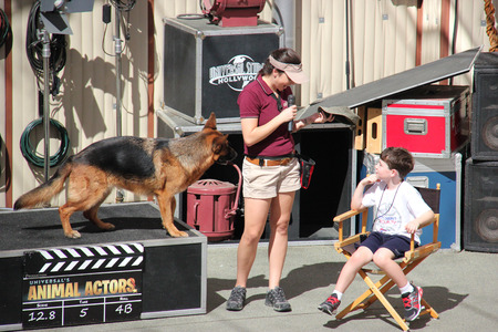 Los Angeles, California, USA - March 12, 2015: The trainer and trained dog are performing in Animal Show at Universal Studios Hollywood.