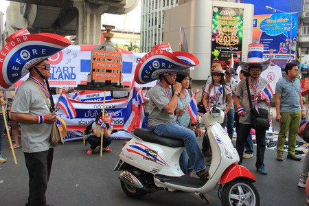 loyalist: Bangkok, Thailand - January 26, 2014: Protestors who hold an anti-government rally use different many products with Thailand Flag colors as a symbol of nationalist and blow whistles to protest against the amnesty bill. Editorial