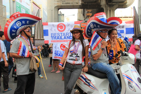 af: Bangkok, Thailand - January 26, 2014: Protestors who hold an anti-government rally use different many products with Thailand Flag colors as a symbol of nationalist and blow whistles to protest against the amnesty bill. Editöryel