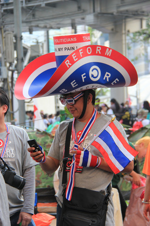 nationalist: Bangkok, Thailand - January 26, 2014: Protestors who hold an anti-government rally use different many products with Thailand Flag colors as a symbol of nationalist and blow whistles to protest against the amnesty bill. Editorial