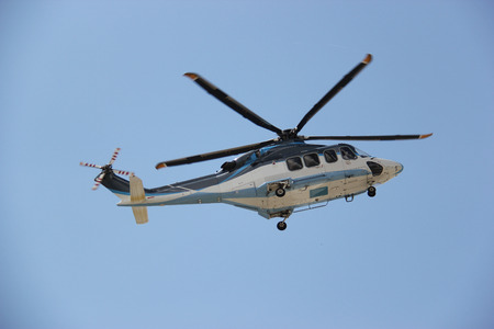 Helicopter is flying in bright blue sky. photo