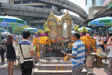 phrom: Bangkok Thailand  April 16 2015: People are paying respect to the Erawan Shrine which is a Hindu shrine housing a statue of Phra Phrom the Thai representation of the Hindu creation God Brahma. Editorial