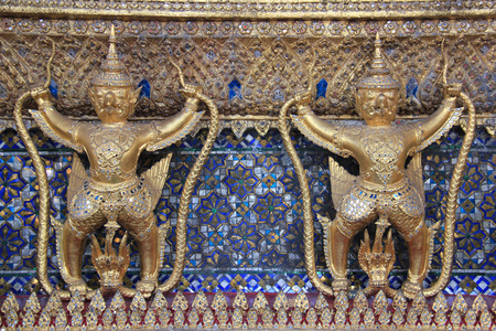 appears: Garuda a large birdlike creature or humanoid bird that appears in both Hinduism and Buddhism is decorated on the wall of Emerald Buddha Temple in Bangkok Thailand.
