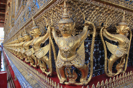 Garuda a large birdlike creature or humanoid bird that appears in both Hinduism and Buddhism is decorated on the wall of Emerald Buddha Temple in Bangkok Thailand. photo