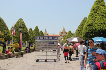 appropriately: Bangkok Thailand  April 21 2015: The sign at the entrance of Emerald Buddha Temple informs tourists to enter the temple on the right side so that the officers can check if they dress appropriately for the temple or not. Editorial