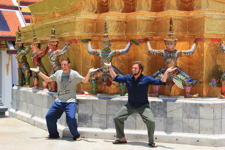 emerald city: Bangkok Thailand  April 21 2015: Tourists have a good time taking a photo with the guardian at Emerald Buddha Temple in Bangkok Thailand.