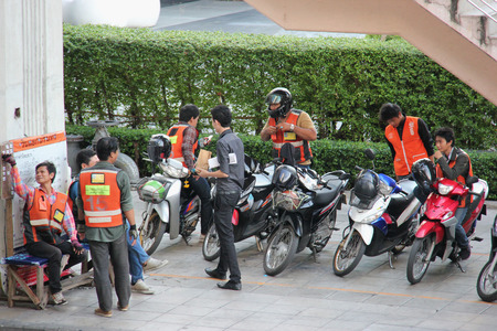 autorick: Bangkok Thailand  April 28 2015: Motorcycle Taxis with orange vests are common form of public transportation in Bangkok. Locals use the service when they need to get somewhere fast. They are popular for delivery service as they tend to drive fast and weav
